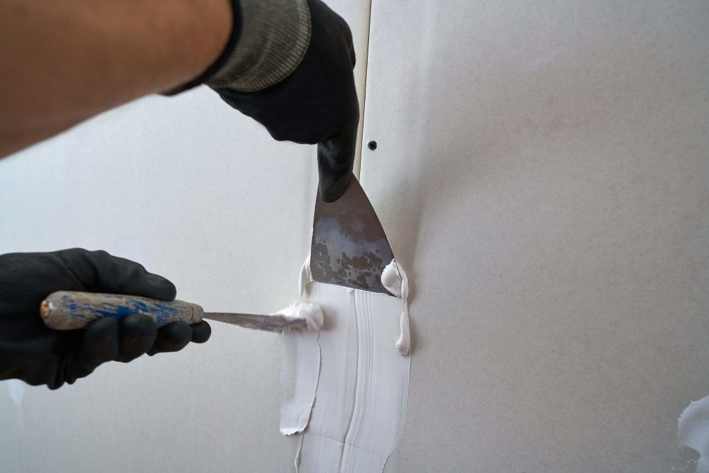 Contractor laying plastering on a gyprock wall